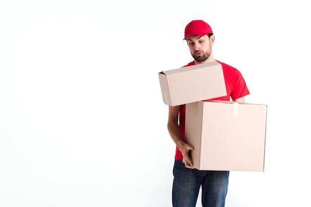Mensajero tratando de mantener todos los buzones de paquetería
