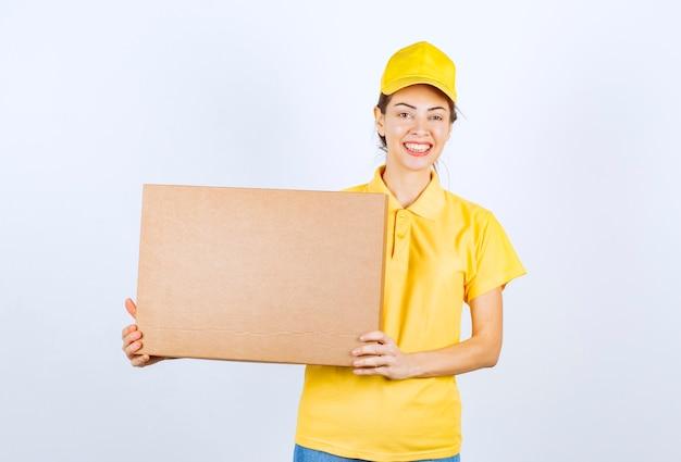 Mensajero de uniforme amarillo entregó un paquete de cartón a la dirección correcta.