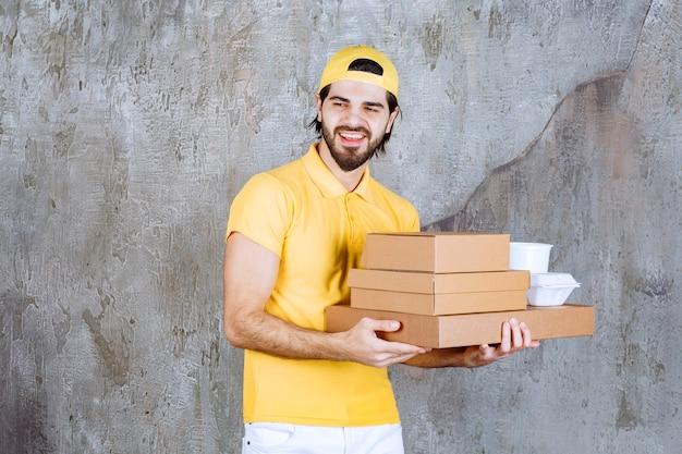 Mensajero en uniforme amarillo con paquetes de comida para llevar y cajas de cartón