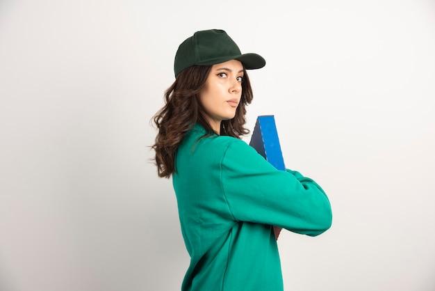 Mensajero en uniforme verde sosteniendo firmemente la caja de pizza.