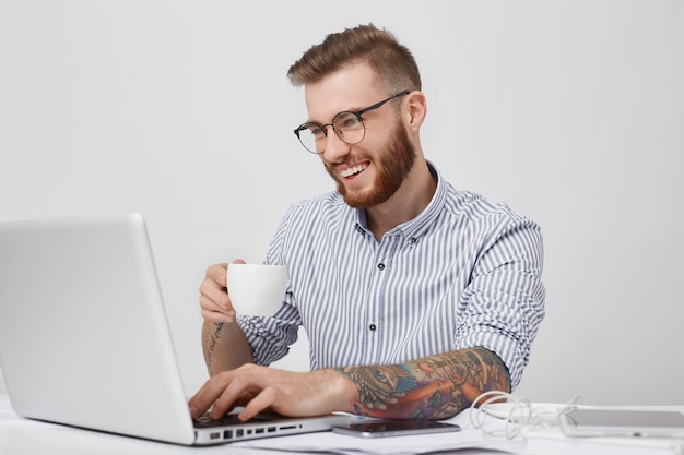 Mensajes positivos de estudiante masculino en redes sociales con amigos, tiene sonrisa agradable