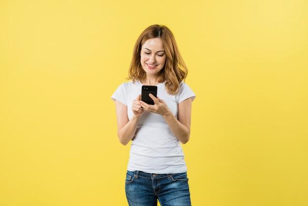 Mensajes que mandan un sms rubios sonrientes de la mujer joven en el teléfono móvil contra fondo amarillo