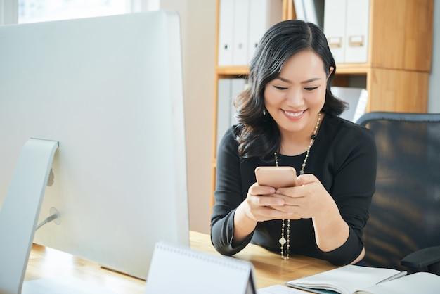 Mensajes de texto empresaria en la oficina