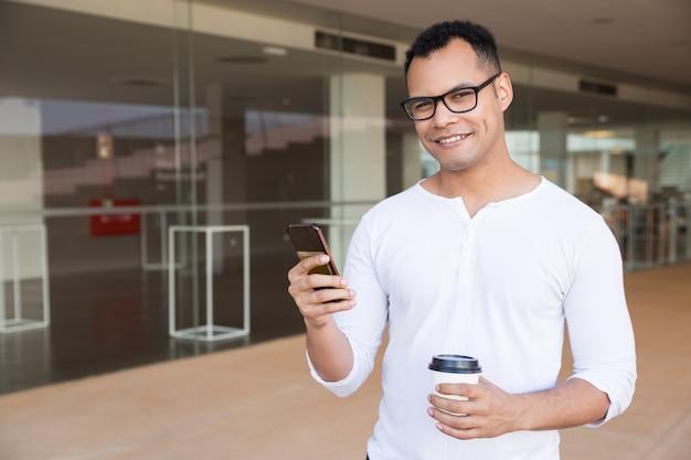 Mensajes de texto del hombre en el teléfono, sosteniendo el café para llevar, mirando a la cámara