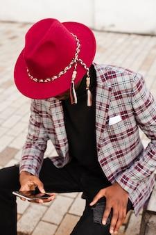 Mensajes de texto de hombres jóvenes con estilo en su teléfono móvil