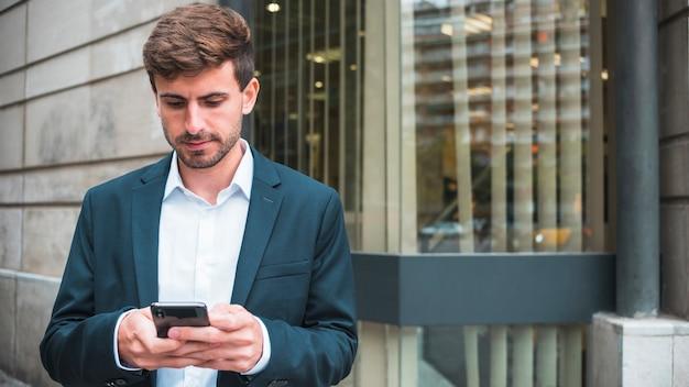 Mensajes de texto de joven empresario en el teléfono inteligente