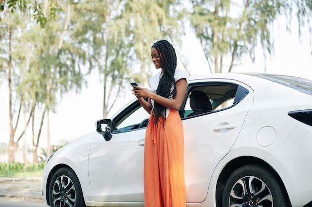 Mensajes de texto mujer de pie en el coche