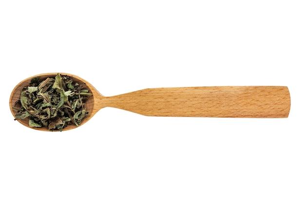 Menta seca en una cuchara de madera sobre un fondo blanco.