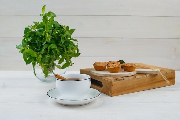 Menta en un tarro de albañil con una taza de té, tortas en la tabla de cortar