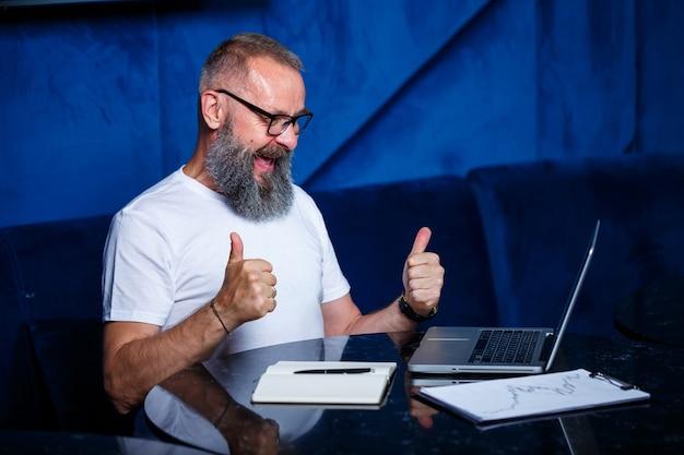 Mentor de sexo masculino adulto, director, empresario con gafas y traje estudiando documentos mientras está sentado en la mesa. concepto de jornada laboral