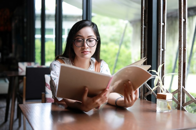 Menú abierto de la mujer asiática para ordenar en café café y restaurante y sonriendo para el tiempo feliz