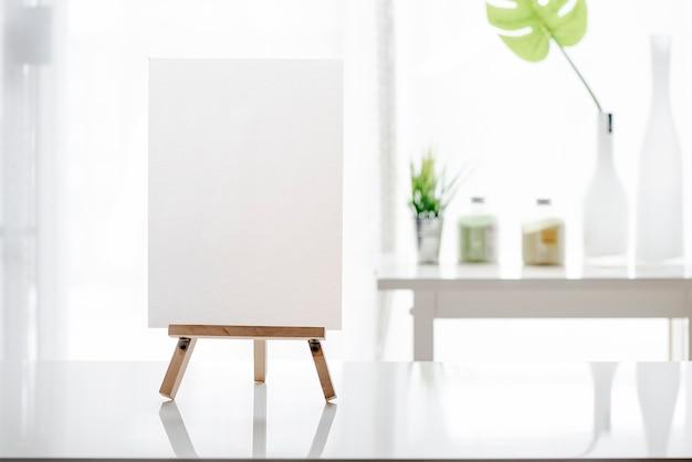 Menú blanco en blanco maqueta en soporte de madera en mesa blanca