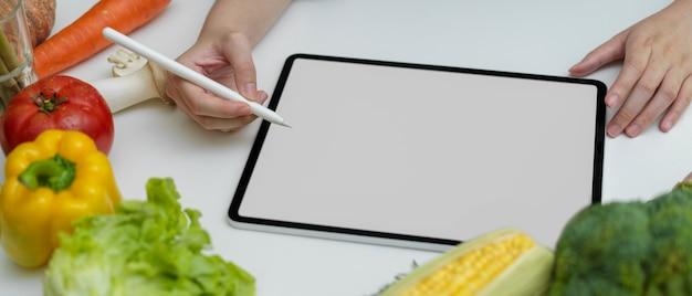 Menú de búsqueda femenina para la cena en la tableta de la pantalla en blanco en la mesa de la cocina blanca con verduras frescas