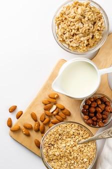 Menú de comida dietética para el desayuno con un tazón de avena con nueces y tarro de leche sobre tabla de madera