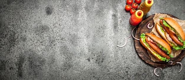 Menú de comida rápida. barbacoa de carne de perritos calientes con hierbas, salsa de tomate y mostaza caliente. sobre fondo rústico.