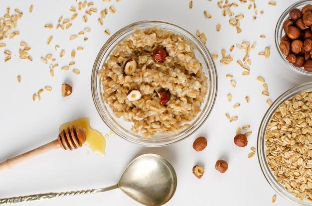 Menú equilibrado de alimentos dietéticos para el desayuno con un plato de gachas de avena con avellanas y miel