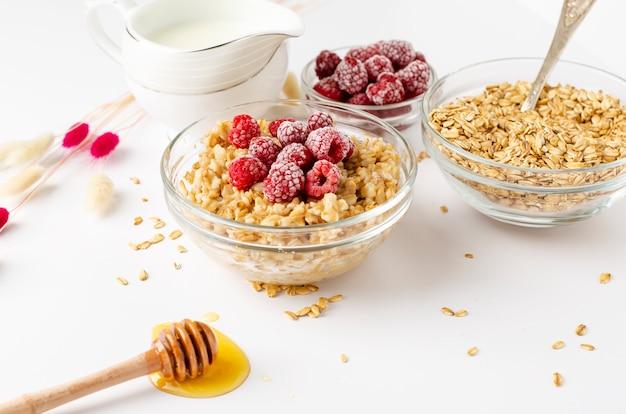 Menú equilibrado de alimentos dietéticos para el desayuno con un plato de gachas de avena con frambuesas y cazo de miel
