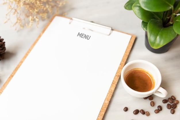 Menú maqueta de papel con taza de café en el restaurante para el texto de la lista de diseño de entrada.