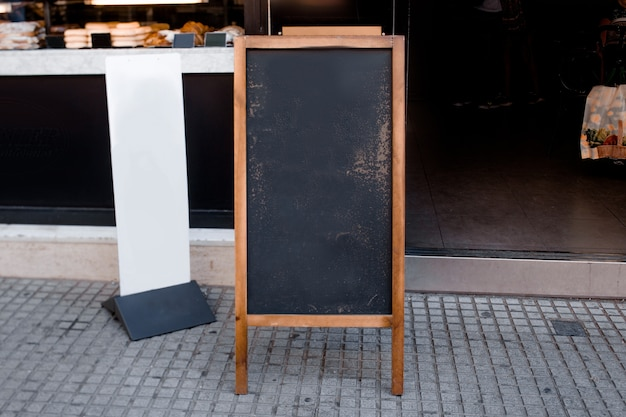 Menú de pizarra en blanco y cartelera blanca frente al restaurante en la calle
