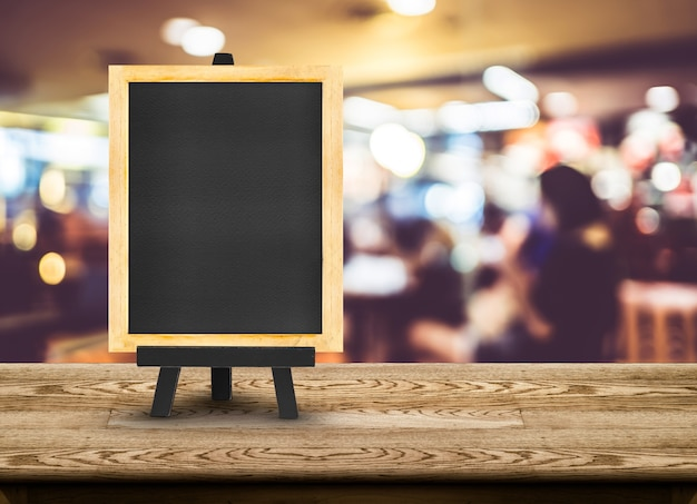 Menú de pizarra con caballete en la mesa de madera con fondo de restaurante de desenfoque