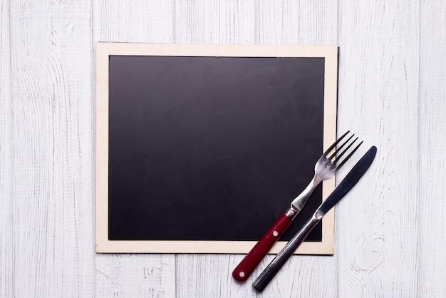 Menú pizarra con cuchillo y tenedor
