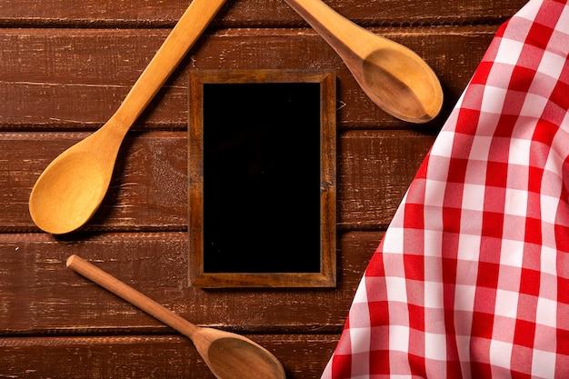 Menú del restaurante. vista superior del menú de pizarra en el escritorio de madera rústica con cucharas y servilleta roja. vista superior.