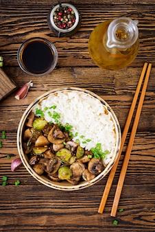 Menú vegano. comida dietética arroz hervido con champiñones y coles de bruselas al estilo asiático. vista superior. endecha plana.