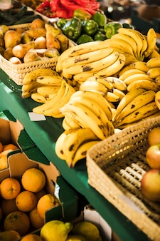 Mercado de frutas con varias frutas y verduras frescas de colores.