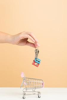 Mercado inmobiliario, casa en carrito de compras y llaves