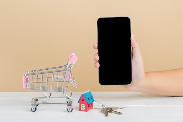 Mercado inmobiliario con casa, carrito de compras y teléfono.