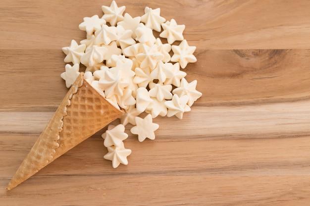 Merengues blancos en cono de helado. fondo de madera