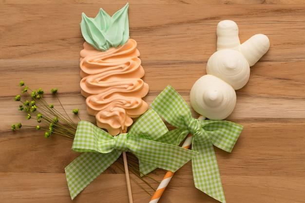Merengues lindos del conejito y de la zanahoria de pascua en fondo de madera