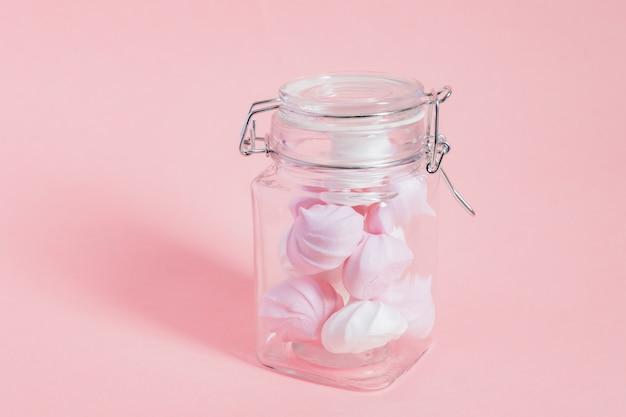 Merengues retorcidos blancos y rosados en un frasco de vidrio sobre fondo rosa