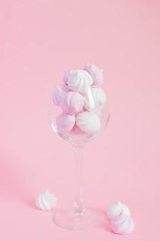 Merengues retorcidos blancos y rosados en un vidrio de vid sobre fondo rosa