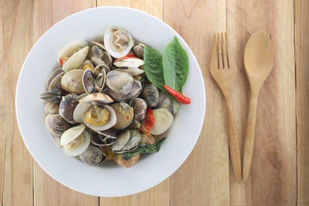La meretrix del soplo o la casta de meretrix es seashell en el plato blanco en fondo de madera.