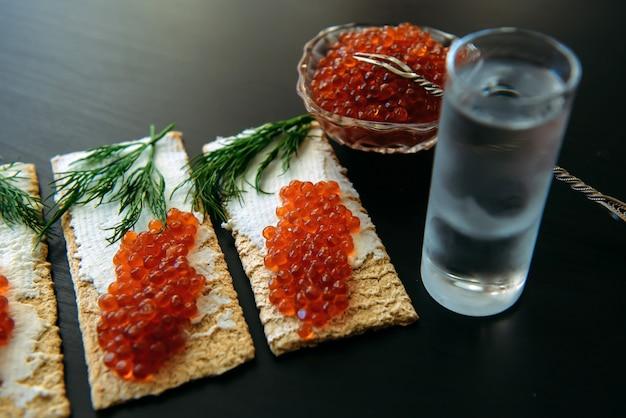 Merienda con caviar rojo y vaso de vodka fría sobre fondo de madera negra.
