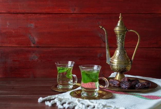 Merienda cerca de fechas en placa de vidrio con té de mentha en el fondo