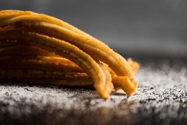 Merienda española de churros con vista frontal de azúcar