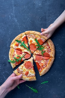 Merienda familiar, manos de madre e hijo tomando rebanadas de pizza de pepperoni. almuerzo o cena tradicional italiana. concepto de comida rápida y comida callejera.