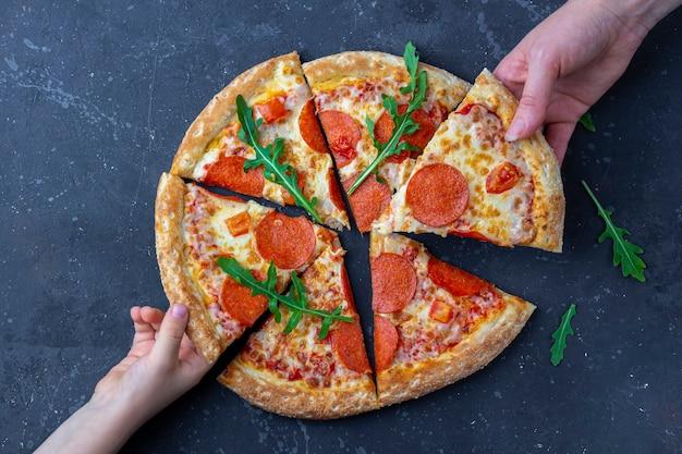 Merienda familiar, manos de madre e hijo tomando rebanadas de pizza de pepperoni.