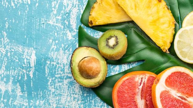 Merienda de frutas y vitaminas en hoja monstera