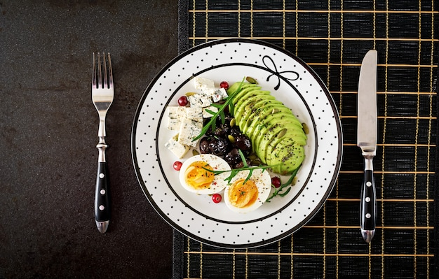 Merienda o desayuno saludable - plato de queso azul, aguacate, huevo duro, aceitunas sobre una superficie negra. vista superior