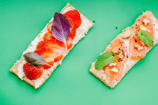 Merienda con pan crujiente, queso crema, fresa y pomelo sobre un fondo verde