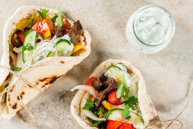 Merienda saludable, almuerzo. gyros sándwich envueltos en griego tradicional - tortillas, pan pita con relleno de verduras, carne de res y salsa tzatziki