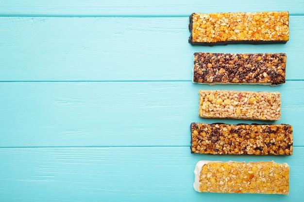 Merienda saludable, barras de muesli con pasas y bayas secas sobre un fondo azul.