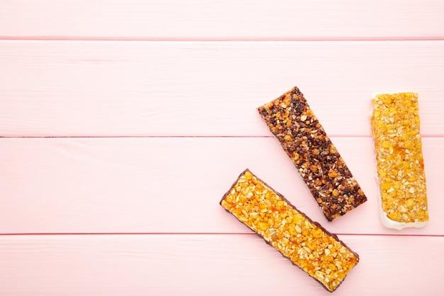 Merienda saludable, barras de muesli con pasas y bayas secas sobre un fondo rosa