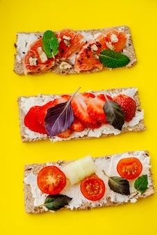 Merienda saludable con pan crujiente, queso crema, fresa, pomelo, tomate y pepino sobre un fondo amarillo