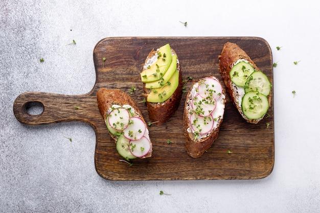 Merienda saludable con pan de grano, ricota, aguacate, pepino, rábano y mostaza micro verdes sobre tabla de madera, vista superior. desayuno vegetariano