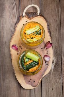 Merienda tradicional coreana de pepinos kimchi en un frasco de vidrio: pepinos marinados con zanahorias, pimiento picante y ajo, con aceite vegetal, en un soporte de madera.