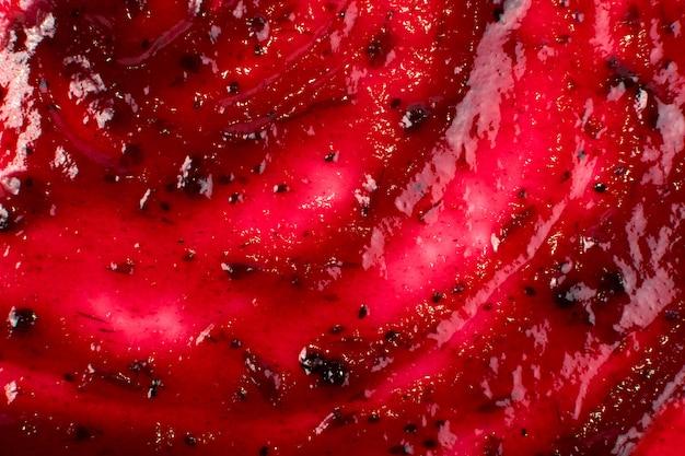 Mermelada de bayas de color rojo oscuro esparcida sobre fondo plano o